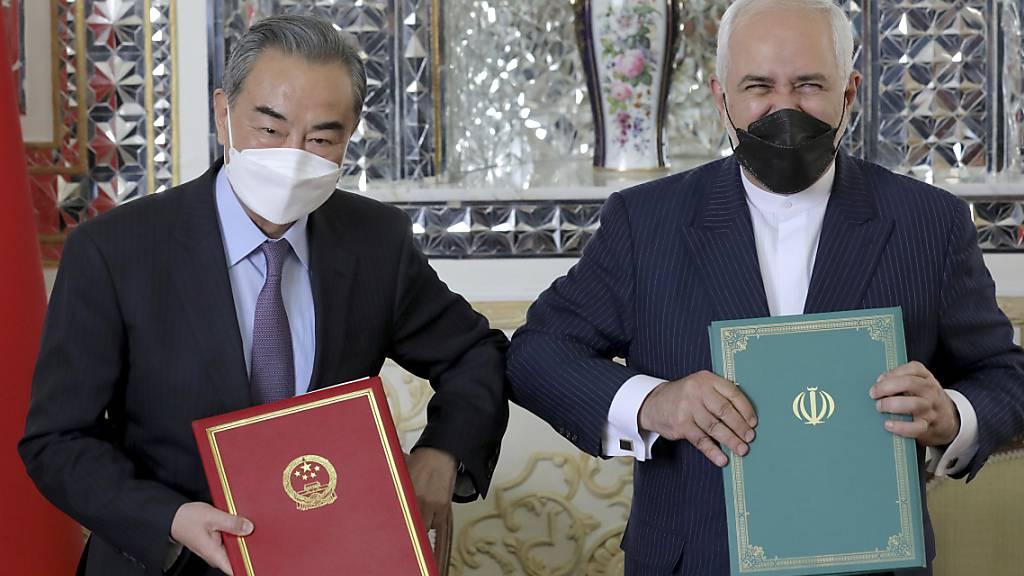 Mohammad Javad Zarif (r), Außenminister des Iran, und sein chinesischer Amtskollege Wang Yi nach Unterzeichnung eines Kooperationsabkommens. Foto: Ebrahim Noroozi/AP/dpa