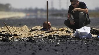 Israelische Polizisten untersuchen das Einschlagloch einer Rakete aus Palästina (Archiv)