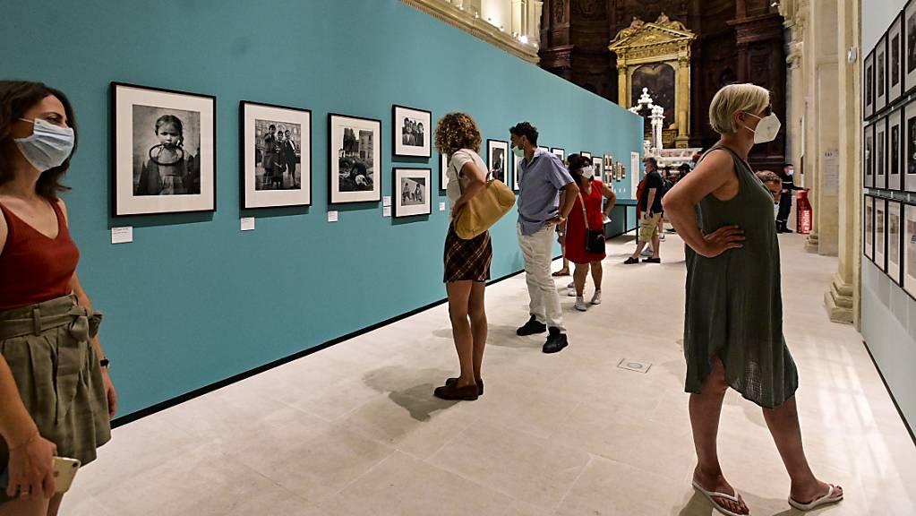 Besucher betrachten Fotografien in der Ausstellung der schweizerisch-französischen Fotografin Sabina Weiss auf dem Fotografie-Weltfestival. Foto: Vondrou? Roman/CTK/dpa