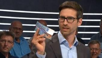 Initiativskomitee-Mitglied Raffael Wüthrich argumentiert mit dem Hunderter in der Hand.