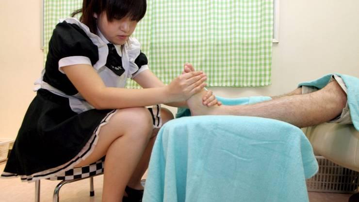 Eine Maid verpasst einem Kunden eine Fussmassage.