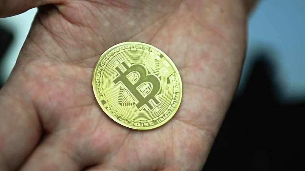 ARCHIV - Ein Mann hält eine nachgemachte Münze mit dem Bitcoin-Logo in den Händen. Foto: Nicolas Armer/dpa