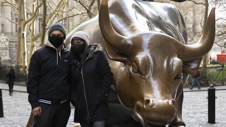 Ein Touristenpaar aus Australien posiert vor dem Bullen an der Wall Street in New York, der für die Börsen-Hausse steht. Die Masken zeigen: Längst müsste dort ein Bär stehen.