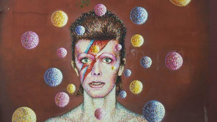 """An einer inoffiziellen Trauerfeier auf dem Burning Man Festival für David Bowie schminkten sich die Trauergäste das """"Bowie Face"""", wie es hier auf einem Graffito zu sehen ist. (Archivbild)"""