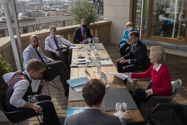EU-Ratspräsident empfängt Macron, Merkel und von der Leyen samt Berater auf der Terrasse seines Büros im EU-Ratsgebäude zu einem Nebentreffen, um möglich Kompromisse auszuloten.