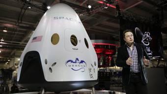 Elon Musk spricht vor einem Modell des Raumschiffs «Dragon» der Firma SpaceX. (Archivbild)