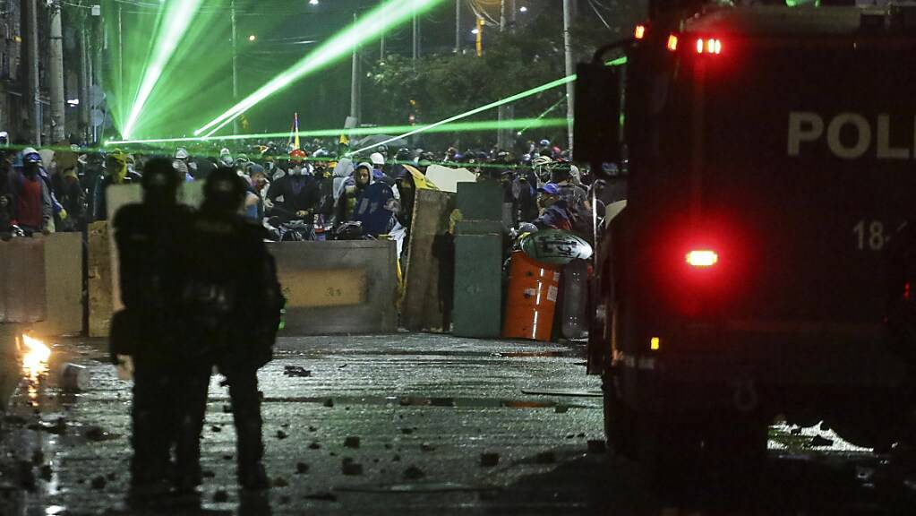 Anti-Regierungs-Demonstranten zielen während eines Protests mit Lasern auf Polizisten.
