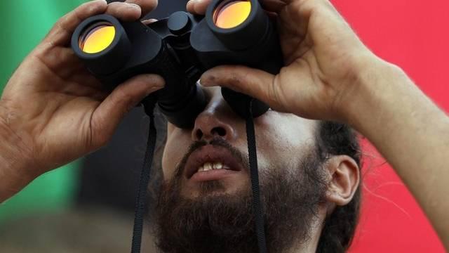 Ein libyscher Rebelle beobachtet die Lage durch einen Feldstecher