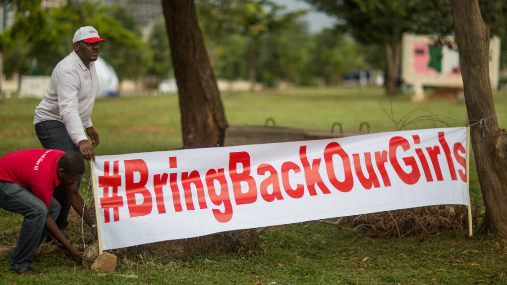 ARCHIV - Aktivisten der Bewegung «Bring back our Girls» (Bringt unsere Mädchen zurück) stellen am 12.06.2014 auf einer Kundgebung in Abuja, Nigeria, ein Transparent mit der Aufschrift «#BringBackOurGirls» auf. Foto: picture alliance / dpa