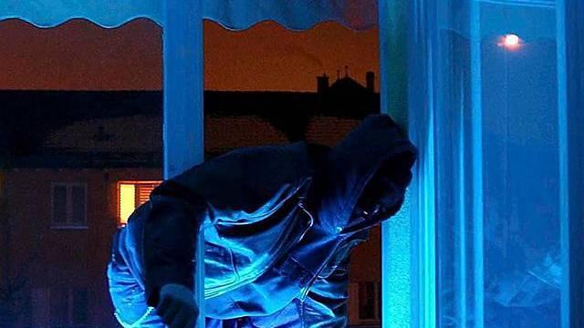 Einbrecher steigt durch das Fenster ein