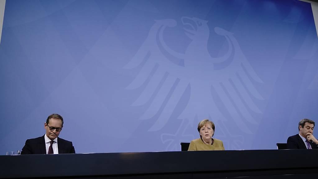 Bundeskanzlerin Angela Merkel (CDU), nimmt neben Markus Söder (CSU, r), Ministerpräsident von Bayern und CSU-Vorsitzender, sowie Michael Müller (SPD), Regierender Bürgermeister von Berlin, an der Pressekonferenz nach den Beratungen von Bund und Ländern teil. Foto: Michael Kappeler/dpa-pool/dpa