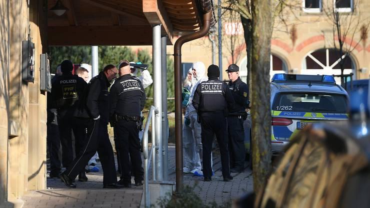 Nach Schüssen in Rot am See im Nordosten Baden-Württembergs steht ein Polizist an einem Haus. Hier sollen mehrere Menschen getötet worden sein. Ein Tatverdächtiger sei festgenommen worden, sagte die Polizei.