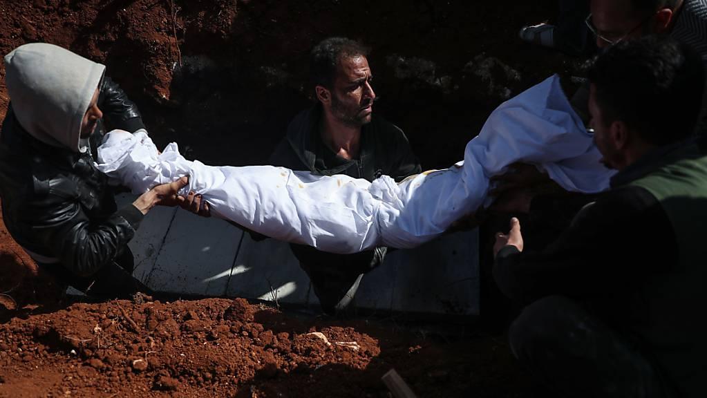 Syrische Männer tragen während einer Beerdigung auf einem Friedhof den Leichnam einer Person, die bei einem Raketenangriff auf ein Krankenhaus getötet wurden. In Syrien sind bei einem Angriff von Regierungstruppen auf ein Krankenhaus nach Angaben von Menschenrechtlern mindestens fünf Menschen getötet worden.