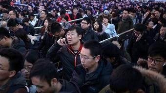 """Das Neujahrsfest gilt als """"Völkerwanderung"""". Passagiere stehen Schlange bei der Sicherheitskontrolle der Metrostation am Bahnhof Pekings. Die Regierung rechnet mit 413 Millionen Bahnreisen während der Neujahrsfeiern. (Archivbild)"""