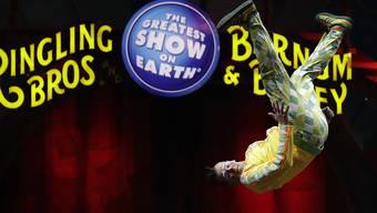 Ein Clown fliegt vor dem Logo des Zirkus. (Archiv)
