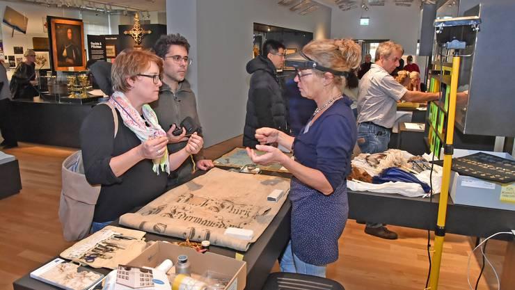 Eine Museumsmitarbeiterin (links) erklärt im Historischen Museum zwei Besuchern ein Ausstellungsstück.