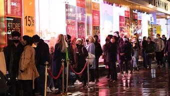 Menschen stehen am letzten Samstag vor Weihnachten auf der Oxford Street in London vor einem Geschäft Schlange. Foto: Stefan Rousseau/PA Wire/dpa