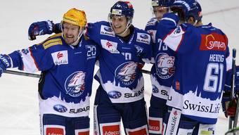 Die Zuercher um Mathias Seger, links, und Cedric Haechler, zweiter von links, jubeln nach dem 4-3 beim Eishockeyspiel der National League A ZSC Lions gegen den SC Bern