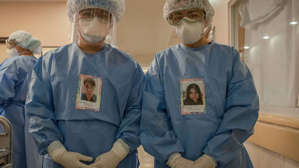 Dr. Lilian Revelez (l) und Maria Fernanda Negrete (r) stehen in Schutzkleidungen mit ihren Porträts vor der Intensivstation für Covid-19-Patienten in der Fachklinik für Lungen- und Atemwegserkrankungen INER. Foto: Jacky Muniello/dpa