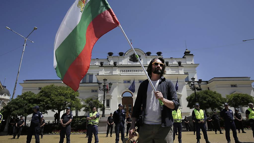 Ein Mann hält während einer Protestaktion vor dem bulgarischen Parlament die Fahne des Landes. Foto: Valentina Petrova/AP/dpa
