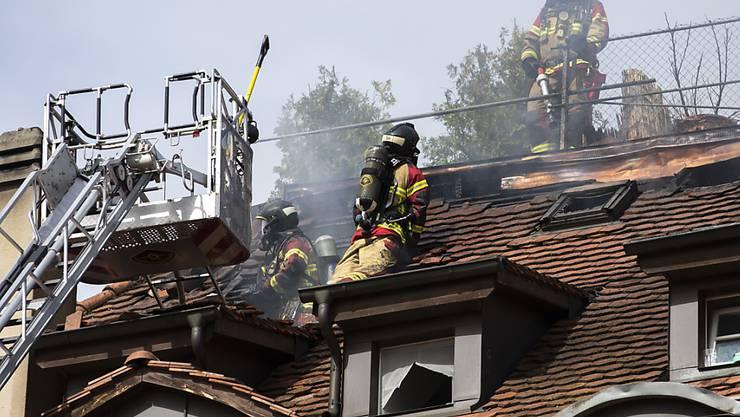 Feuerwehrleute löschen einen Brand in einem Dachstock eines Hauses am Eigerplatz in Bern. (KEYSTONE/Peter Klaunzer)