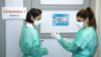 Zwei Pflegerinnen bereiten sich im Lausanner Uni-Spital auf einen Besuch in einem Isolationszimmer vor.