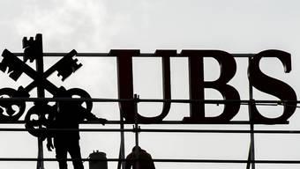 Die UBS profitiert im dritten Quartal von einem Sondereffekt: Arbeiter neben dem UBS Logo in Zürich.