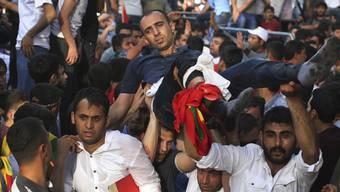 Männer tragen einen Verwundeten Mann nach der Explosion an der Kundgebung