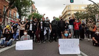 Demonstranten sitzen auf einer Strasse im Stadtbezirk Villa de Vallecas. Tausende Menschen haben in Madrid gegen die Abriegelungen von mehreren einkommensschwachen Gebieten der spanischen Hauptstadt zur Eindämmung der Corona-Pandemie protestiert. Foto: David Obach/EUROPA PRESS/dpa