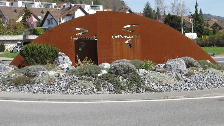 Kunstwerke in der Freiluftgalerie Limmattal findet man nicht nur entlang von Wegen, an Häusern und auf Plätzen, sondern auch mitten auf der Strasse. In verschiedenen Gemeinden wurden oder werden die Verkehrskreisel kreativ gestaltet. Oft mit dem Ziel, den Dorfeingang zu verschönern. Ein Kunstwerk, das eine ungewöhnliche Vorgeschichte kennt, steht auf dem Kreisel in Geroldswil. Im Jahr 2005 geriet dieser in den Fokus der Kantonspolizei Zürich, tauchte in der Verkehrsunfallstatistik als Unfallschwerpunkt auf. Grund dafür war die zu breite Fahrspur im Kreisel, die es erlaubte, praktisch ohne einlenken zu müssen und mit hoher Geschwindigkeit durch den Kreisel zu fahren. 2007 wurde das Innenrondell verbreitert und die Dorfstrasse vor dem Kreisel verengt, damit man abbremsen muss, bevor man sich in den Kreisverkehr einreiht. Für die Gemeinde war damit die Zeit gekommen, sich dem äusseren Erscheinungsbild des Kreisels zu widmen. Gleichzeitig wurden immer wieder Leute auf der Gemeinde vorstellig. Sie forderten, den Kreisel schöner zu gestalten. Die Idee, ein Kunstwerk aufzustellen, war geboren. Seither zieren zwei drei Meter hohe rostbelassene, sichelförmige Metallplatten mit dem nachts beleuchteten Gemeindelogo den Kreisel. Geschaffen wurde das Werk von Pietro Paladino, dem Abteilungsleiter Bau und Werke der Gemeinde. (zim)
