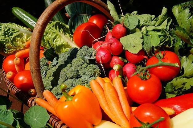Verschiedenes buntes Gemüse, wie Tomaten, Brokkoli und Karotten liegen in einem Korb.
