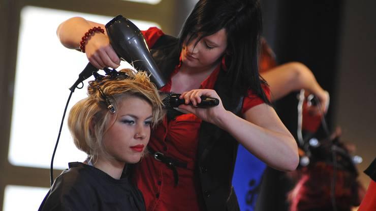 Mit Föhn und Bürste werden die Haare frisiert.
