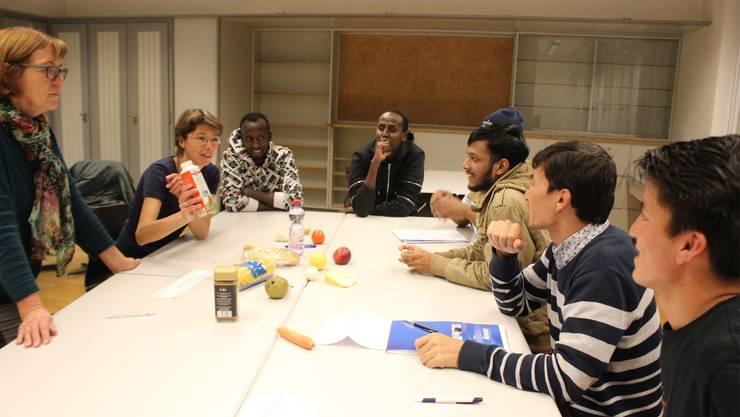 Therese Frei (stehend) und Elisabeth Latscha erklären den Flüchtlingen, wie die Grundnahrungsmittel heissen.