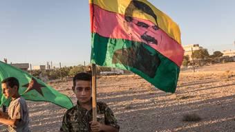Ein kurdischer Junge demonstriert mit einer Fahne des Kurdenführers Abdullah Öcalan für mehr Selbstbestimmung.