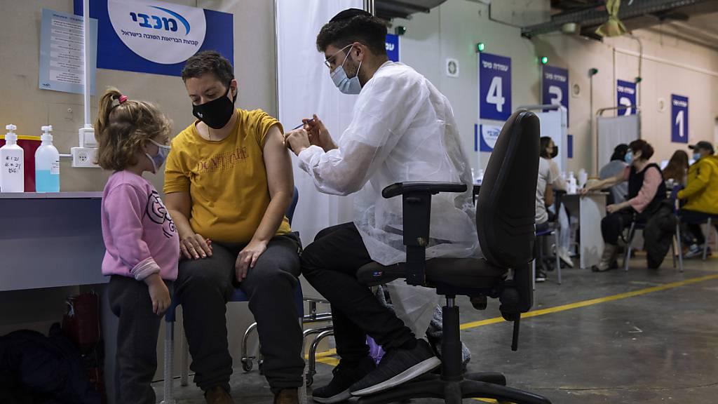 Eine israelische Frau bekommt von einer medizinischen Fachkraft in einem Impfzentrum eine Impfdosis mit dem Corona-Impfstoff von Biontech/Pfizer. Foto: Oded Balilty/AP/dpa