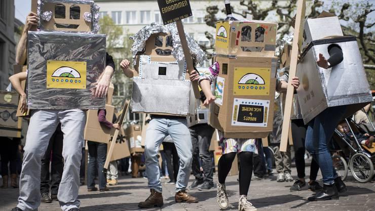 Kinder und Erwachsene, als Roboter verkleidet, demonstrieren in Zürich für das bedingungslose Grundeinkommen.