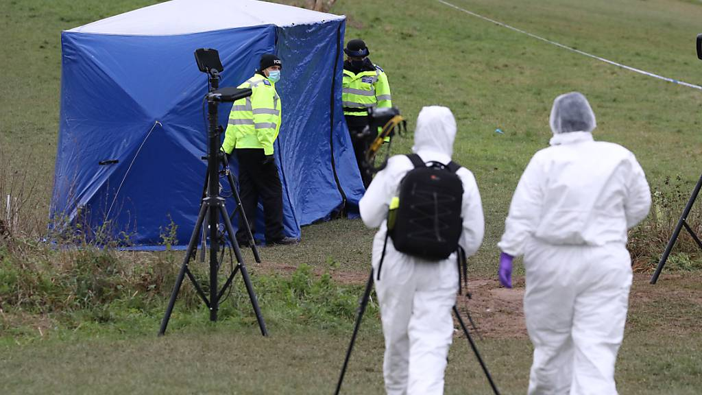 ARCHIV - Zwei Gerichtsmediziner gehen zu einem Zelt am Tatort auf dem Bugs Bottom Feld. Fünf Jugendliche sollen hier am 03.01.2021 einen 13-jährigen Jungen erstochen haben. In England hat ein Gericht zwei 14-Jährige wegen Mordes schuldig gesprochen. Den beiden Tätern droht lebenslange Haft. Foto: Jonathan Brady/PA Wire/dpa