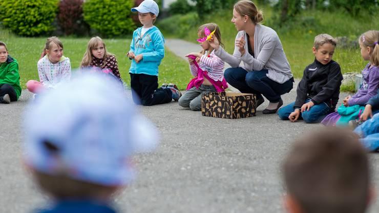 Vor dem Basteln wird im Kreis gesungen und die Sarah Widmer zeigt die Dschungelblumen.