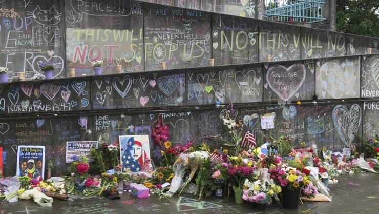 """Mit Blumen und Kerzen gedenken Einwohner von Portland, Oregon, der Männer, die zwei junge Frauen vor ihrem Angreifer schützen wollten. Der Mann hatte die Frauen mit anti-muslimischen Hasstiraden angegriffen. Bei seinem ersten Gerichtstermin bezeichnetet sich der mutmassliche Mörder als """"Patriot""""."""