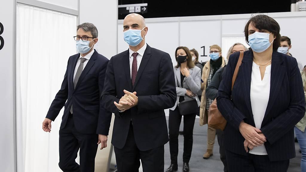 Bundesrat Alain Berset, flankiert vom Basler Gesundheitsdirektor Lukas Engelberger und Regierungspräsidentin Elisabeth Ackermann während eines Besuchs im Impfzentrum Basel Stadt.