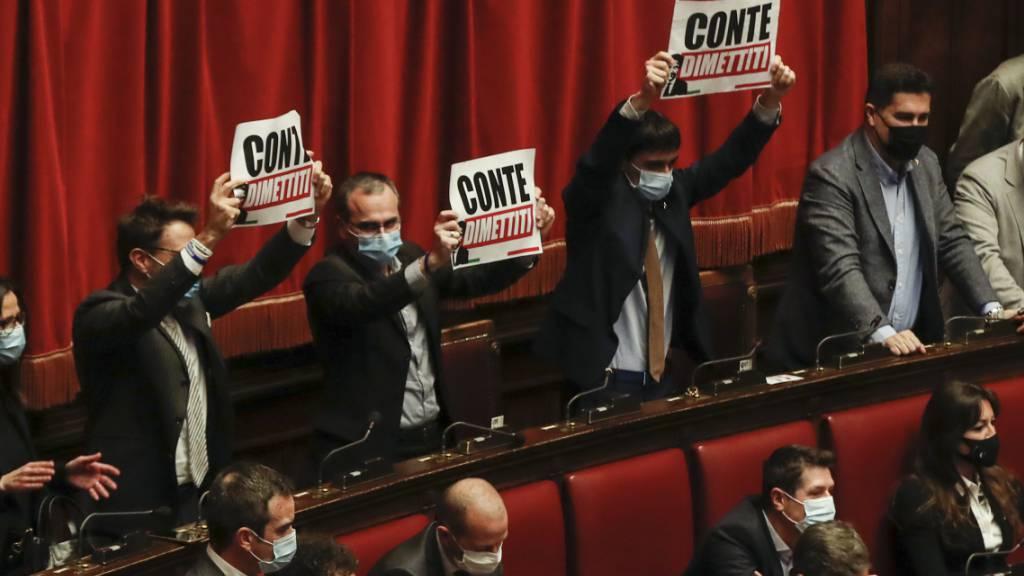 Protest vor dem Vertrauensvotum: Abgeordnete halten während einer Rede von Italiens Ministerpräsident Conte Plakate mit der Aufschrift «Conte, tritt zurück» in die Höhe. Foto: Alessandra Tarantino/AP/dpa