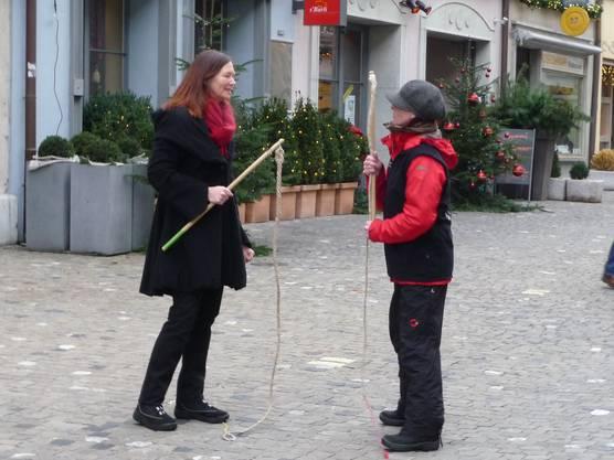 Eine Passantin übt das Chlausklöpfen