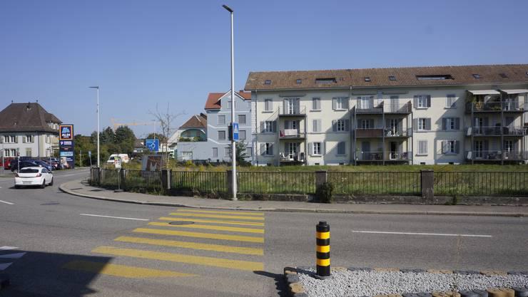 Auf der Wiese an der Kreuzung Bahnhofstrasse/Wilerstrasse ist der Neubau eines Mehrfamilienhauses geplant. Der Neubau lehnt sich in der Ausrichtung an das bestehende Mehrfamilienhaus (rechts) an. Der Zaun soll erhalten werden.