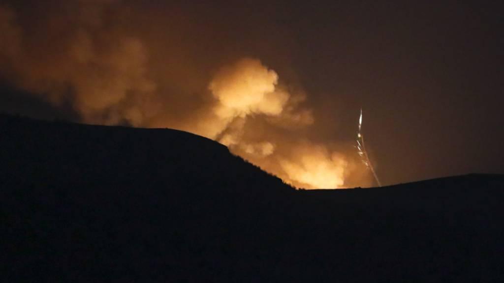 Explosionen sind hinter einem Bergkamm während eines militärischen Konflikts zu sehen.