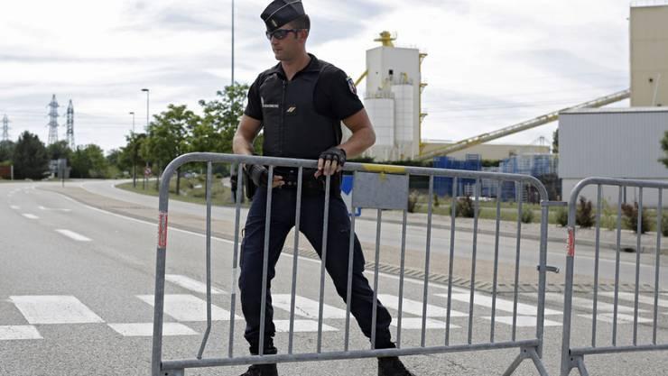 Ein Polizeibeamter sperrt das Gebiet rund um den Tatort ab