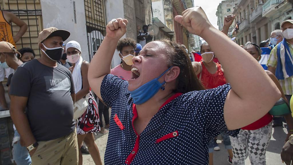 Eine Frau schreit Pro-Regierungs-Parolen, während Anti-Regierungs-Demonstranten in Havanna, Kuba, marschieren. Foto: Ismael Francisco/AP/dpa
