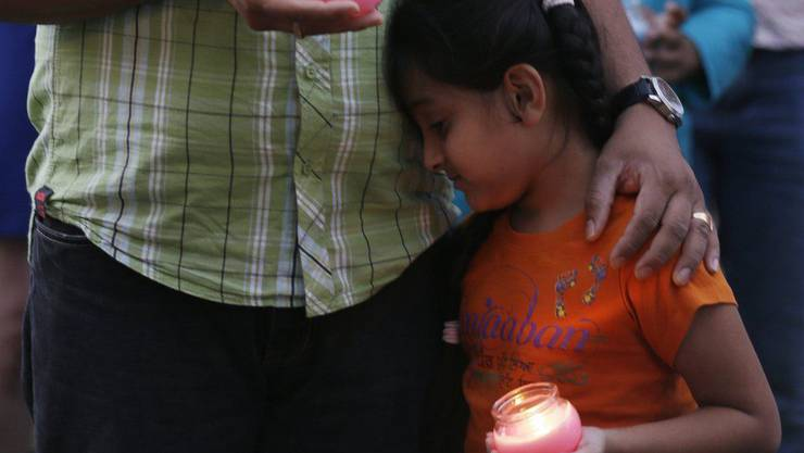 Ein Mann trauert mit seiner Tochter um die Opfer
