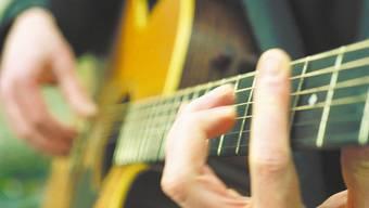 Einzelne Lehrpersonen spielen der Klasse auf der Gitarre vor.